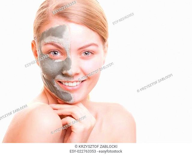 Skin care. Woman applying clay mask on face. Spa