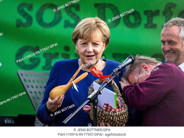 German Chancellor Merkel (CDU) holds wooden salad servers which she got from the resident Roswitha Wellmann at the Michaeli culture festival in the SOS Village...