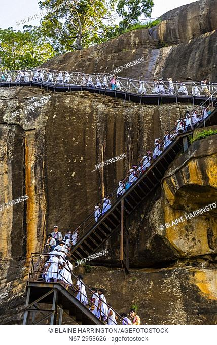 School girls climbing a staircase to the top of Sigiriya Rock (an ancient rock fortress), Central Province, Sri Lanka
