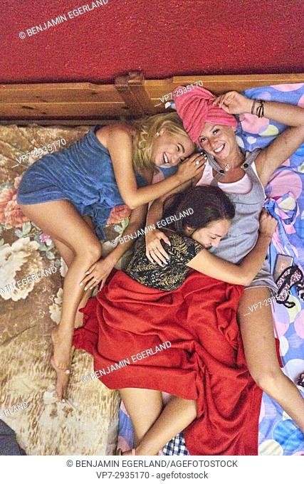 girls, friends chilling together in bed. Russian ethnicity. In Hersonissos, Crete, Greece