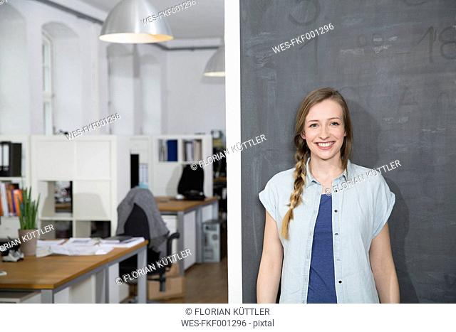Smiling young woman standing at blackboard in office