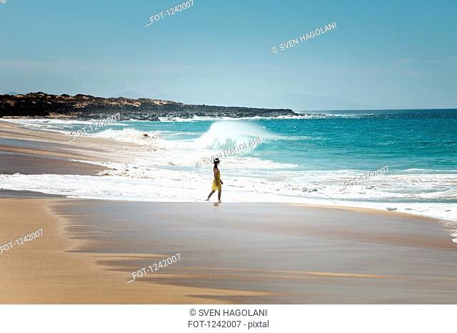 Woman walking on shoreline in La Graciosa, Canary Islands, Spain
