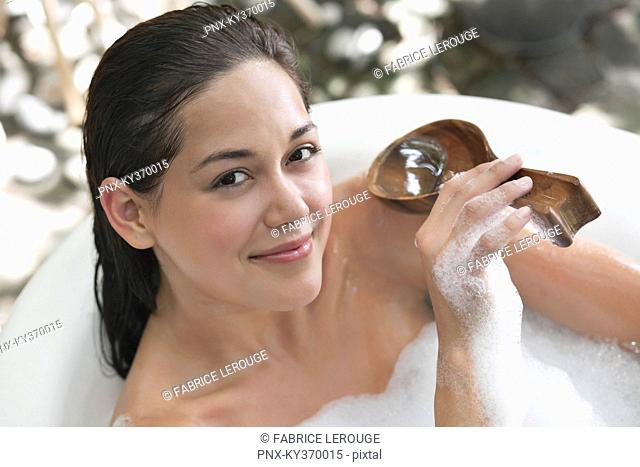Portrait of a beautiful young woman taking bubble bath