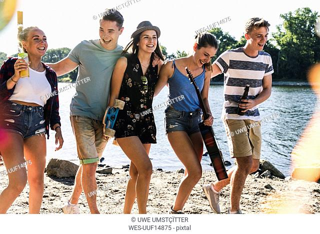Group of happy friends walking arm in arm at the riverside