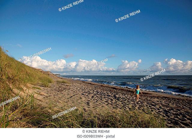 Girl playing on beach, Blowing Rocks Preserve, Jupiter Island, Florida, USA