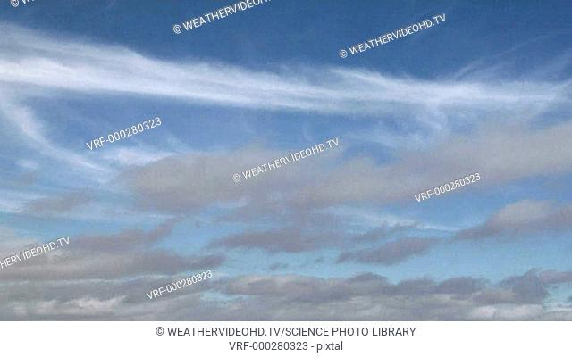 Timelapse footage of cumulus and cirrus cloud moving in different directions due to wind shear. Filmed in Colorado, USA, in autumn