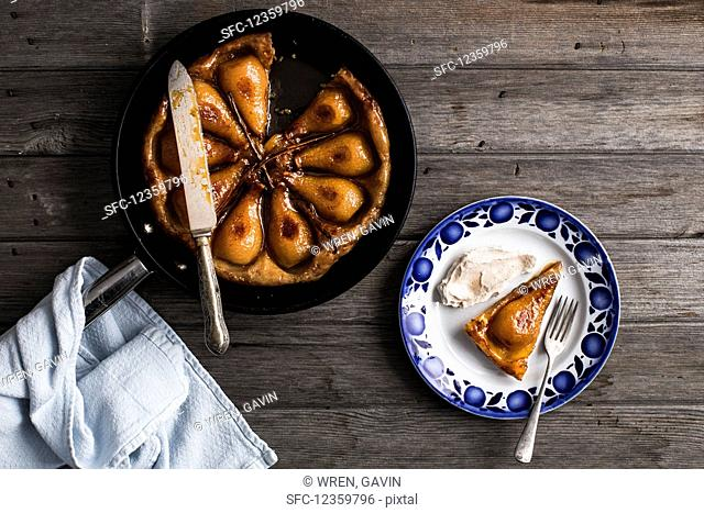 Pear tarte tatin with vanilla pods, puff pastry and cinnamon labneh sweetened with maple syrup in a pan with an aged wood background