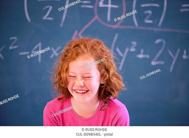 Portrait of cute primary schoolgirl giggling in classroom