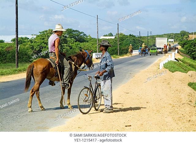 Cowboy talking to a man with a bicycle on the side of a rural road in Cuba