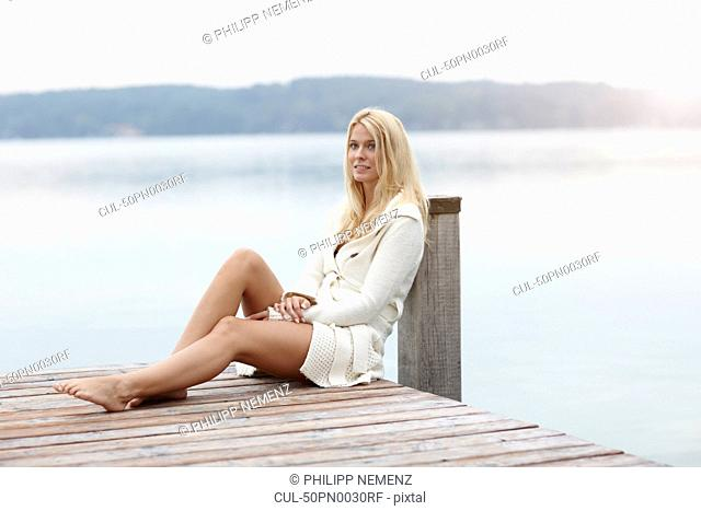 Woman leaning on post on wooden deck