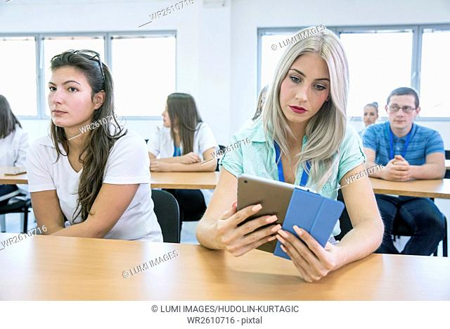 Female student in training class using digital tablet