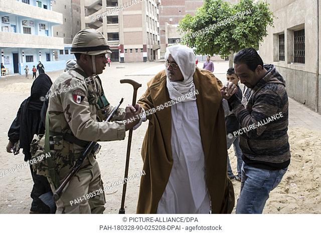 A man and an army soldier help an elderly man to enter a polling station to vote on the 3rd day of the 2018 Egyptian presidential elections, in Monufia, Egypt