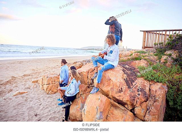 Friends relaxing on beach, Plettenberg Bay, Western Cape, South Africa