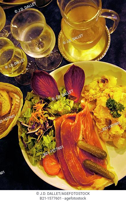 Food: 'truffade' (mix of potatoes with cheese) with cured ham and salad and white wine, Murat, Cantal, Auvergne, France
