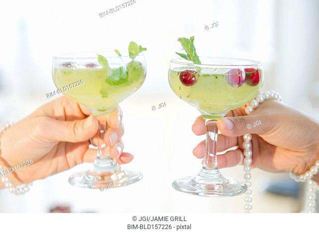 Women toasting with cocktails and pearl necklaces