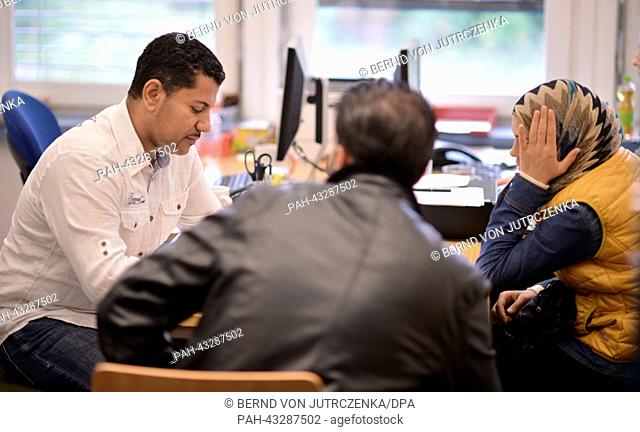 Interpreter Ahmed Yasser speaks with Syrian saylum seekers in an outpost of the Federal Office for Migration and Refugees in Berlin-Spandau, Germany