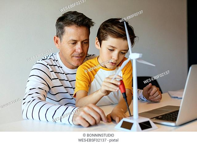 Father and son with laptop assembling wind turbine model
