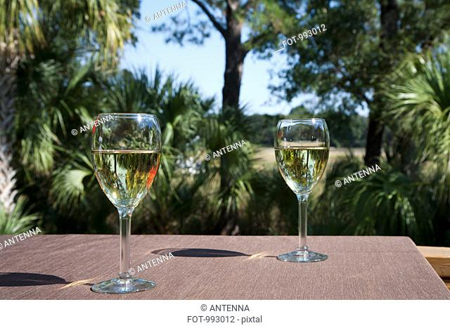 Two glasses of white wine on a table, outdoors