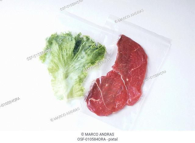 one raw meat beef and a lettuce leaf packaged