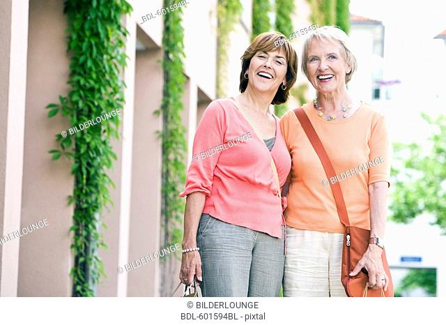portrait of two senior women with shopping bags