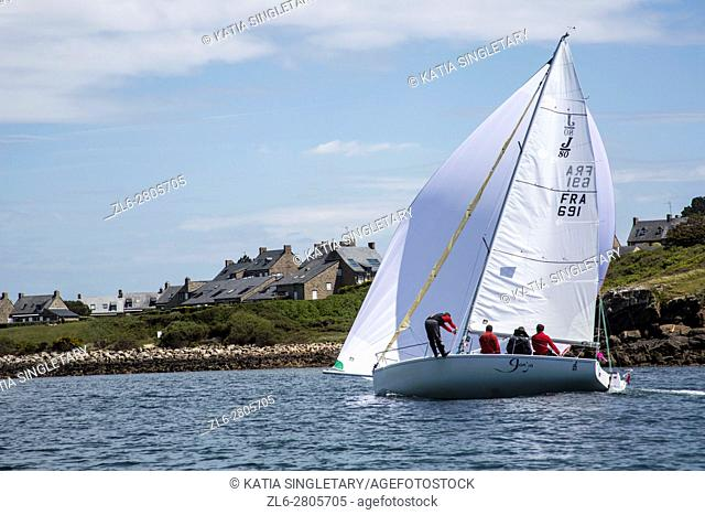 Sail boat with full sail and full wind passing by in the French ocean and on the coast of Bretagne, Brittany, France
