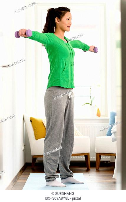 Woman lifting dumbbells with both arms