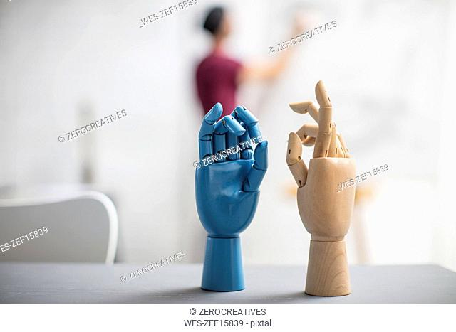 Hand models in studio and artist drawing in background