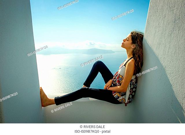 Girl sitting, leaning against wall, sea in background, Oía, Santorini, Kikladhes, Greece