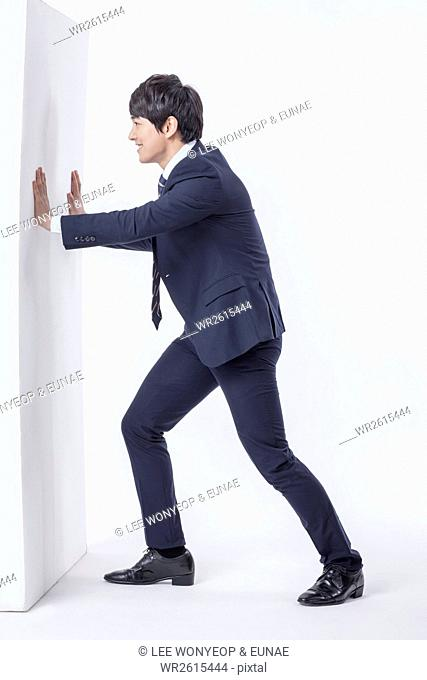 Businessman pushing a wall
