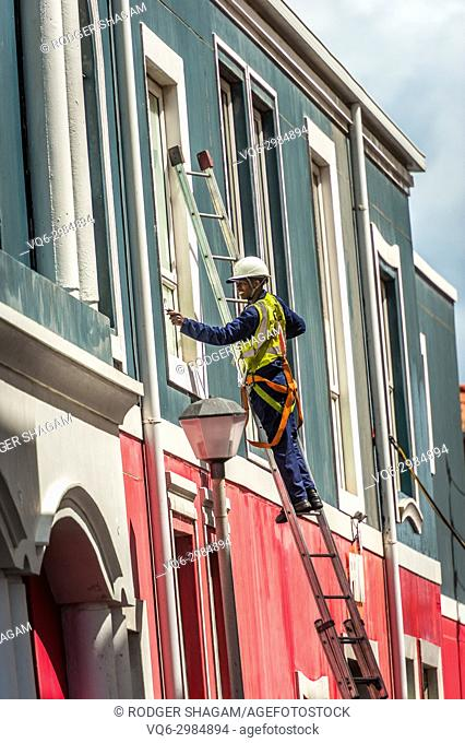Window cleaner standing on a ladder and detailing a window. Cape Town, South Africa