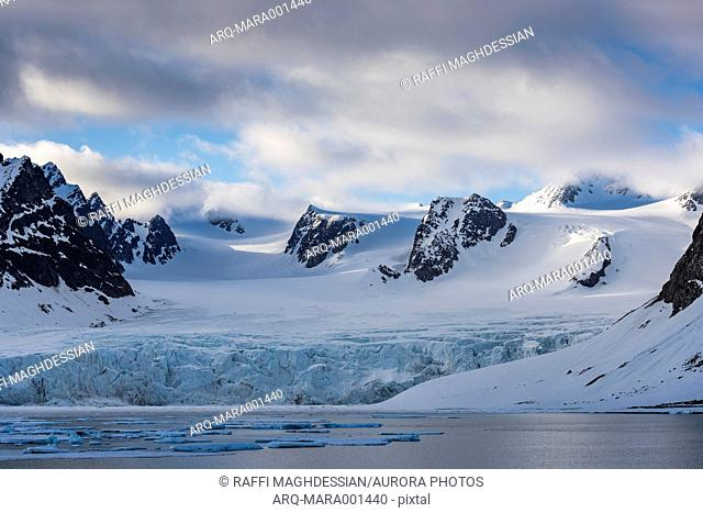 Beautiful natural scenery of glacier in the Arctic with snowy and rocky mountains in the background, Spitsbergen, Svalbard and Jan Mayen, Norway