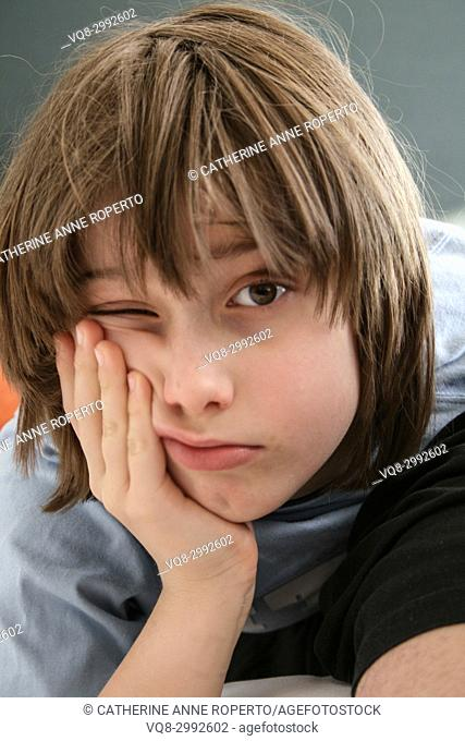 Young boy with messy brown hair leaning his cheek on his hand with one eye open in Brussels, Belgium