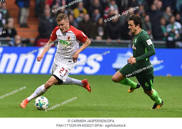 Augsburg's Alfred Finnbogason (L) and Bremen's Thomas Delaney vie for the ball during the German Bundesliga soccer match between Werder Bremen and FC Augsburg...