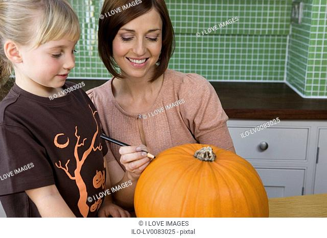 Mother and daughter carving a face in a Hallowe'en pumpkin