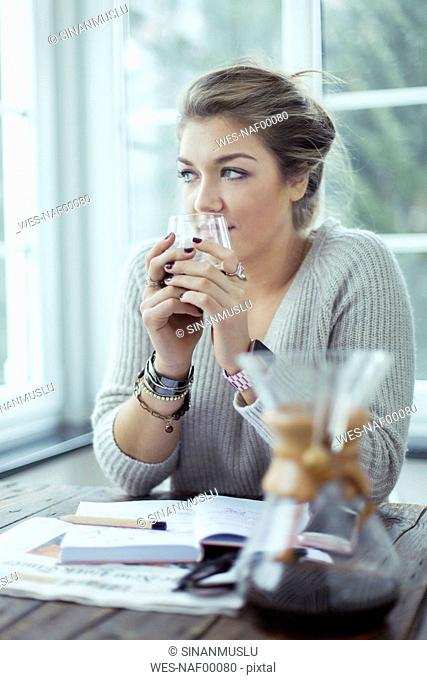 Portrait of young woman with glass of coffee looking through window
