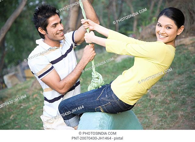 Young couple swinging on a tire swing