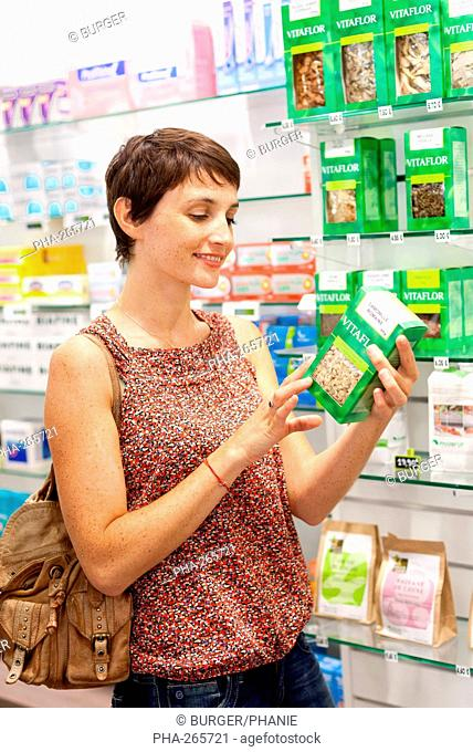 Woman shopping in herbal and phytotherapy products section in pharmacy