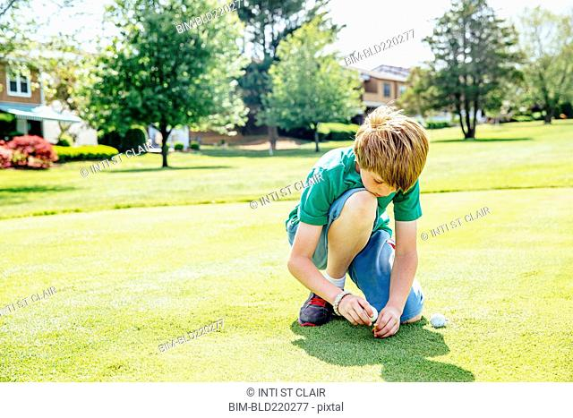 Caucasian boy setting up golf ball on course