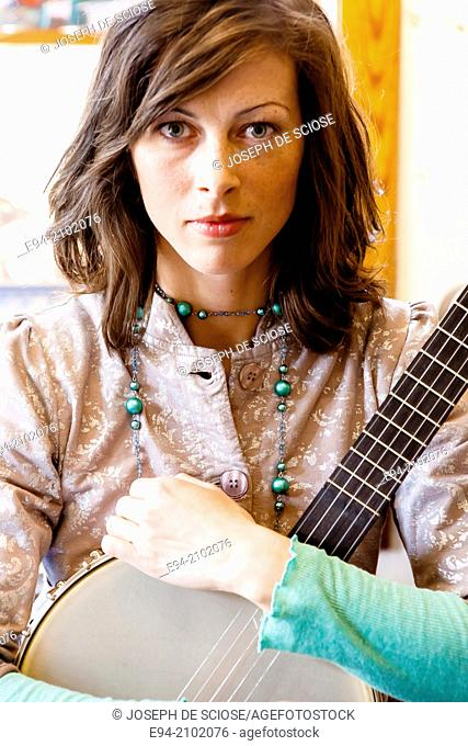 A 28 year old brunette woman holding a banjo on her lap with a serious expression