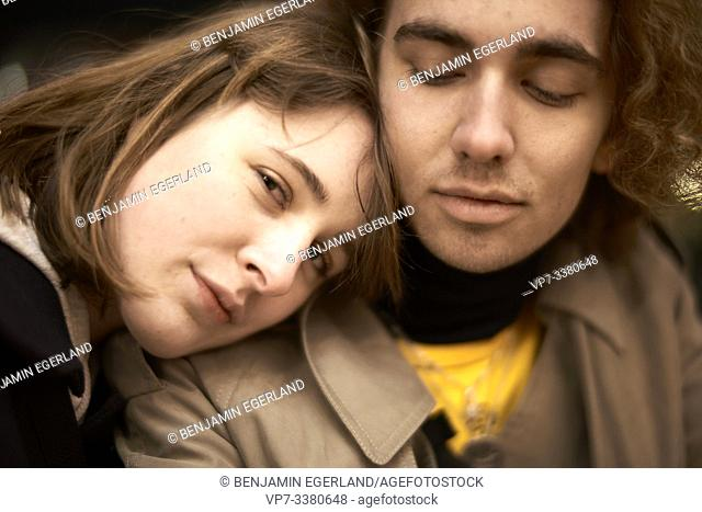 woman resting on shoulders of man