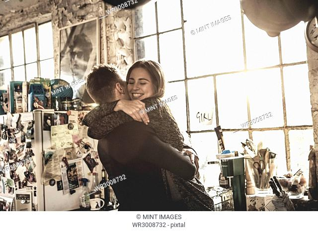 Smiling young woman and young man standing indoors by a window, hugging