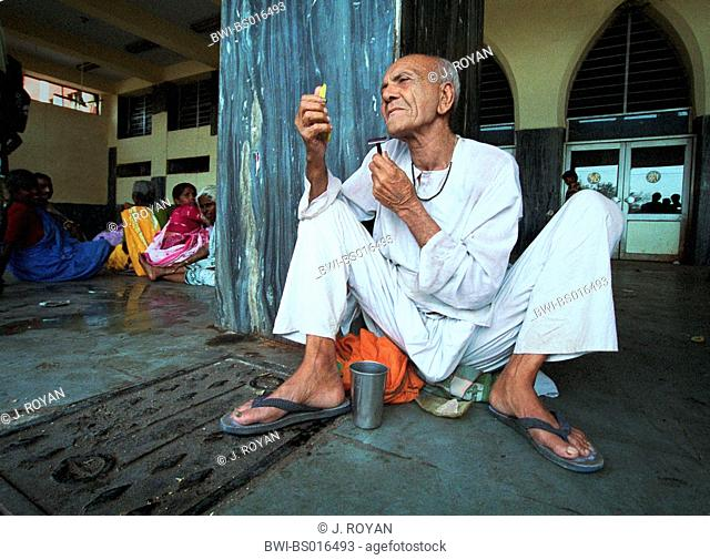 man sitting on the ground and shaving, India, Delhi, New-Delhi