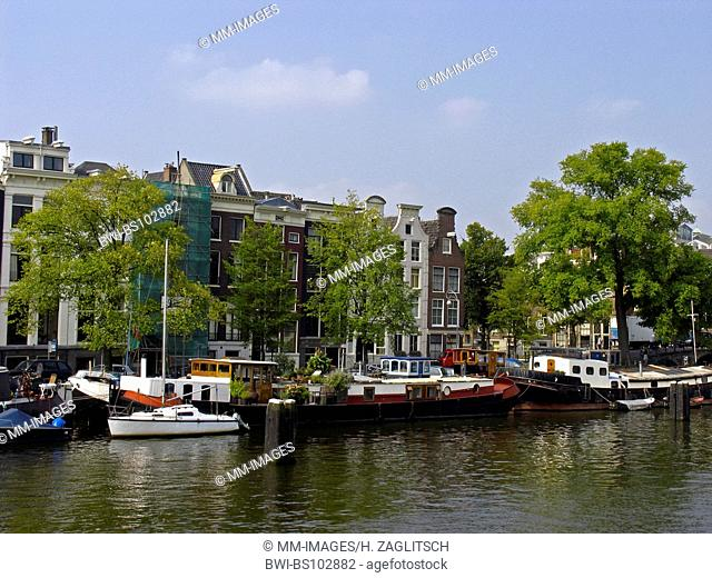 the river Amstel with old canal houses and houseboats, Netherlands