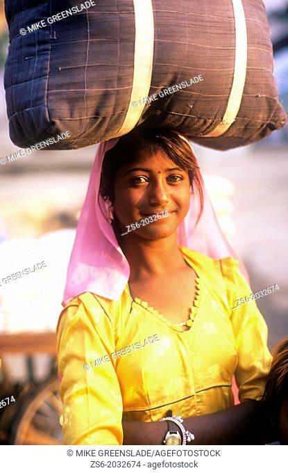 Young indian girl smiling and carrying a large pack on her head, Pushkar, Rajasthan, India