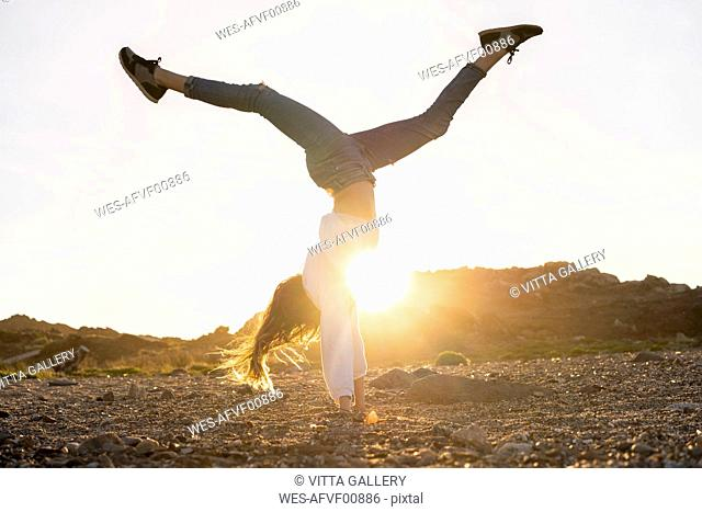 Young woman at the beach, doing handstand at sunset