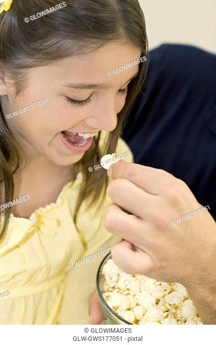 Close-up of a person's hand feeding popcorn to a girl