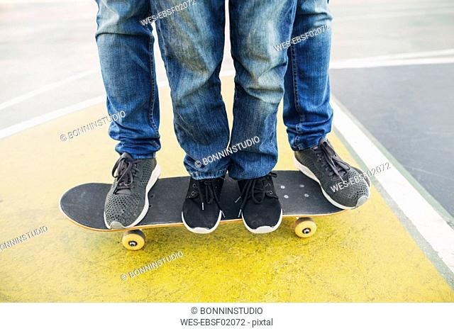 Legs of adult and child on skateboard