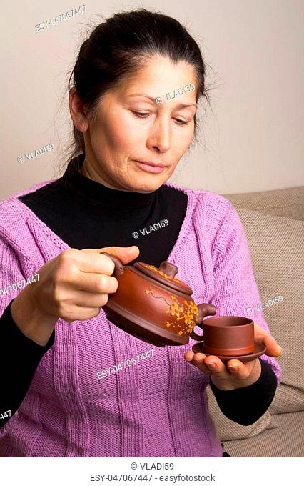 Attractive senior woman pouring tea in cup at home