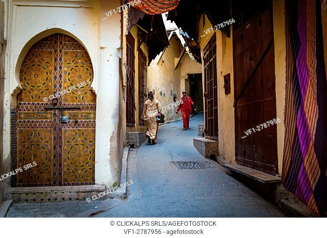 Fes, Morocco, North Africa. Passers in the narrow streets of the medina