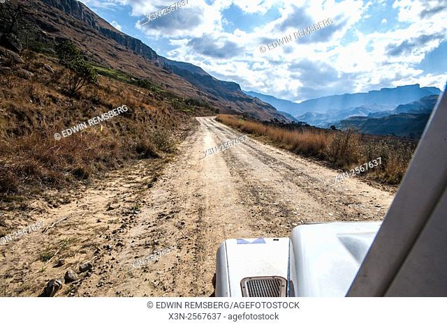 Land Rover Defender driving down a dirt road in Sani pass between South Africa and Lesotho